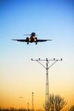 Het vliegtuig landt bij zonsondergang Stock Afbeelding