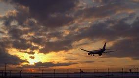Het vliegtuig landt dageraad Vroege ochtend De hemel is oranje op de horizon stock videobeelden