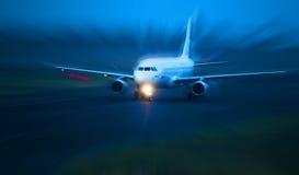 Het vliegtuig neemt van bij schemer Stock Afbeeldingen