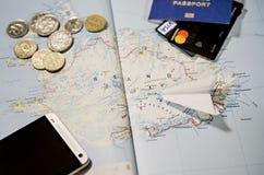 Het vliegtuig, smartphone, het biometrische paspoort, de dollars, de muntstukken en de creditcards liggen op een kaart royalty-vrije stock afbeeldingen