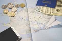 Het vliegtuig, smartphone, het biometrische paspoort, de dollars, de muntstukken en de creditcards liggen op een kaart royalty-vrije stock foto's