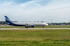 Het vliegtuig stond op de baan op de achtergrond van blauwe hemel met Cirruswolken van start te gaan op het punt Het horizontale  Stock Afbeelding