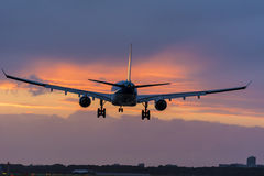Het vliegtuig treft voor het landen bij de baan voorbereidingen Geschotene genomen paarnotulen vóór een aardige bewolkte zonsopga Stock Afbeeldingen