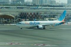 Het vliegtuig van de Vliegdoubai van de begrotingsluchtvaartlijn treft om in de Dubai International-Luchthaven te parkeren voorbe stock foto's