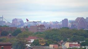 Het vliegtuig van Delta Airlines is het landen, vliegend tegen de achtergrond van Manhattan stock video