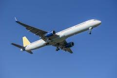 Het vliegtuig verwijdert uit blauwe hemel Stock Foto