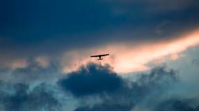 Het vliegtuig vliegt in de hemel bij avond met verbazende kleuren; Stock Fotografie