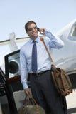 Het Vliegveld van zakenmanusing cellphone at Stock Fotografie