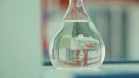 Het vloeibare chemische reagenschemische product in een ronde bodemfles stock videobeelden