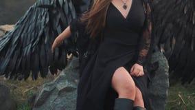 Het vlotte panoramische schieten, meisje met heldere gevoelige hand maakt binnen zacht grote veren van haar sterke vleugels glad, stock footage