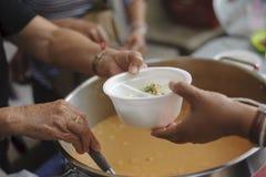 Het voeden van de armen aan handen van een bedelaar Armoedeconcept stock foto's