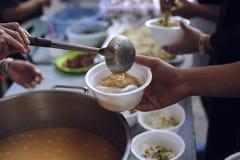 Het voeden van de armen aan handen van een bedelaar Armoedeconcept stock afbeeldingen