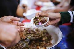 Het voeden van de armen om elkaar in de maatschappij te helpen: concept schenking stock foto