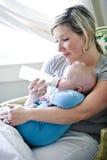 Het voeden van de moeder fles aan de oude baby van zeven maanden stock foto