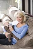 Het voeden van het mamma fles aan baby thuis op laag Stock Foto's