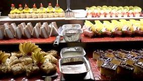 Het voedsel diende op de lijst, de Zweedse lijst: vlees, rijst, deegwaren, salades en diverse cakes en gebakjes stock videobeelden