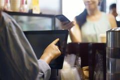 Het voedsel en de drank van de klantenorde, die haar smartphone en nfs geavanceerd technisch gebruiken om een barista voor haar a royalty-vrije stock fotografie