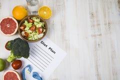 Het voedsel en het blad van document met een dieet plannen op een donkere houten lijst stock afbeelding