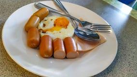 Het voedsel heeft hotdogs en gebraden eieren op een mooie schotel royalty-vrije stock afbeeldingen
