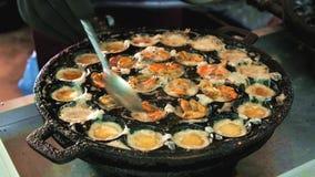 Het voedsel van de straat in Thailand Gebraden die ei met mosselen in het ijzerpan van Kanom Krok worden gekookt stock footage