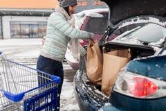 Het voedsel van de vrouwenlading van boodschappenwagentje aan autoboomstam Royalty-vrije Stock Afbeeldingen