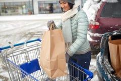 Het voedsel van de vrouwenlading van boodschappenwagentje aan autoboomstam Stock Foto's
