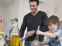 Het Voedsel van vaderand son cooking in Keuken Stock Afbeeldingen