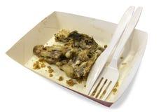 Het voedselafval op document platen met plastic messen en de vorken isoleren Stock Foto