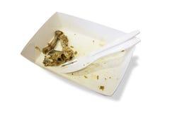 Het voedselafval op document platen met plastic messen en de vorken isoleren Royalty-vrije Stock Afbeelding