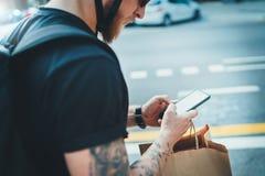 Het voedseldienst van de koeriers de snelle levering thuis Mensenkoerier die een kaart app op mobiele telefoon gebruiken om het a royalty-vrije stock afbeeldingen