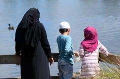 Het voereenden van de immigranten moslimfamilie in een vijver Stock Foto's