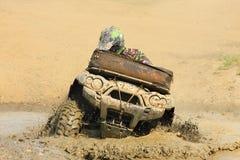 Het voertuig met vier wielen van het ras in een vulklei van modder Stock Foto's