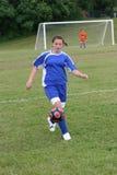 Het Voetbal van de Jeugd van de tiener in Actie betreffende Gebied Stock Foto