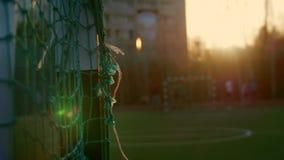Het voetbal van het tienerjarenspel over voetbaldoel bij de zomeravond stock footage