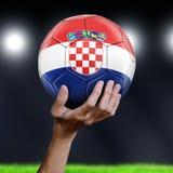 Het Voetbalbal van de mensenholding met Kroatische vlag Stock Foto's