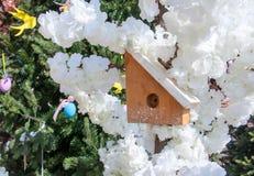Het vogelhuis met hellend wit dak op de achtergrond van de lente bloeit en naaldtakken royalty-vrije stock foto's