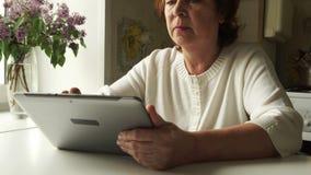 Het VOLGEN: Oude vrouw die een digitale tabletpc thuis met behulp van stock footage