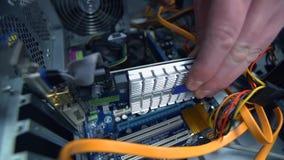 Het volgen van mannelijke handen die grafische kaart opnemen en op motherboard zetten stock videobeelden