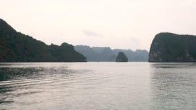 Het volgende panning schot van cruiseboot die door de kalksteeneilanden varen van Ha snakt binnen Baai Vietnam stock videobeelden