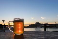 Het volledige glas bier op houten lijst aangaande het kasteel achtergrond van Bratislava, Slowakije stock fotografie