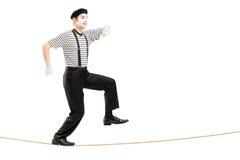 Het volledige lengteportret van een mannetje bootst kunstenaar het lopen op een kabel na Stock Foto