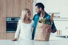 Het volwassen gelukkige paar bevindt zich in keuken met pakket van producten stock afbeelding