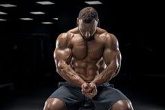 Het volwassen kerelbodybuilder stellen in gymnastiek Stock Foto