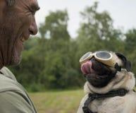 Het volwassen mannelijke glimlachen bij pug hond met beschermende brillen Stock Foto