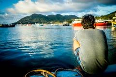 Het volwassen mannelijke hurken op een pijler naast gedokte schepen en mooi kalm water royalty-vrije stock afbeelding