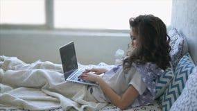 Het volwassen meisje drukt tekst op laptop toetsenbord, liggend onder een deken in bed stock footage