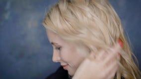 Het volwassen mooie blondemodel met naakte make-up en sloten bekijkt speels camera die, door haar golven stock footage
