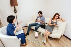 Het volwassen paar zit en bekijkt hun telefoons Zij zijn bored De mensen trekken ` t luisteren aan aan therapeut Doctor proberen stock fotografie