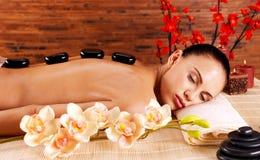Het volwassen vrouw ontspannen in kuuroordsalon met hete stenen op rug Royalty-vrije Stock Foto