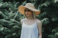 Het vooraanzicht van het meisje in een wit overhemd op de achtergrond is een muur van hagen Royalty-vrije Stock Foto's